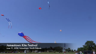 A group of men appears to be dwarfed by this 40-by-60-by-12 paraform kite as it goes aloft Friday at the Kite Fest in southwest Jamestown. The kite when collapsed and boxed up weighs 340 pounds. The red, white and blue heart-shaped kite in the background is 20 feet across and 90 feet long. The Kite Fest continues this weekend at Meidinger Park Addition. JOHN M. STEINER | THE SUN