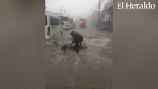 Personas en motocicleta a punto de ser arrastradas por lluvias