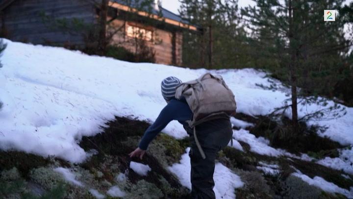 På fjelltur med sekk og hytte i syne