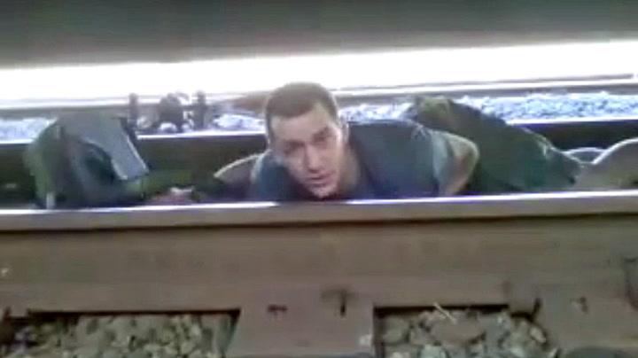 Hjelp! Han sitter fanget under et rullende godstog