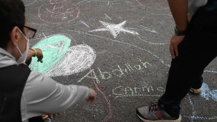 Evacuated Afghan children play with soldiers and draw with chalk at New Jersey military base
