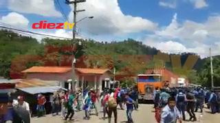nmigrantes hondureños rompen la barrera policial en la frontera con Guatemala con  una rastra