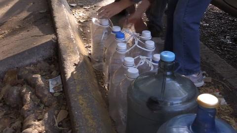 Venezolanos obtienen agua de manantial en medio de escasez