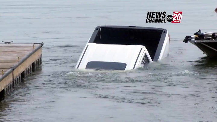 Trucks sinks into lake behind news reporter during filming