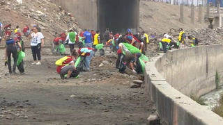 Migrantes venezolanos limpian laderas de río en capital de Perú