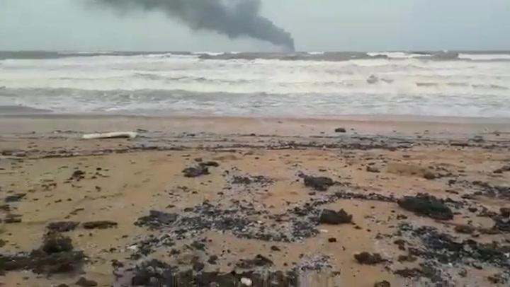 Oil and debris cover the beach as ship burns off Sri Lanka's coast