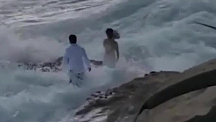 Una ola arrastra mar adentro a una pareja de recién casados que se hacía las fotos de su boda