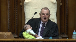 Carga un bebé en brazos mientras preside reunión parlamentaria