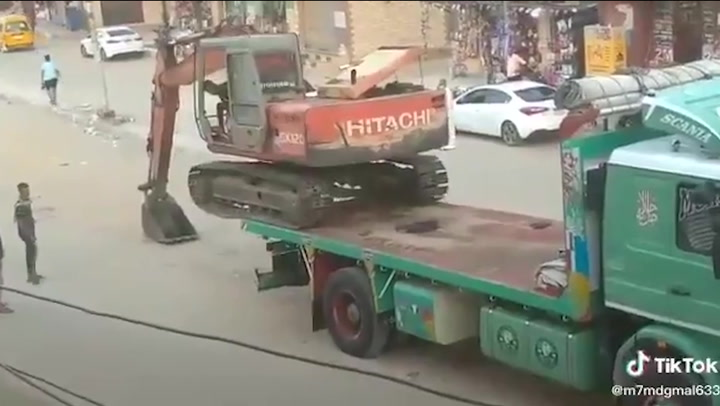 Excavator operator skilfully drives machine off truck in Egypt