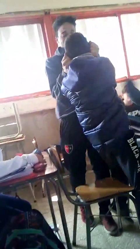 Un video muestra como a un chico lo levanta de las orejas un alumno