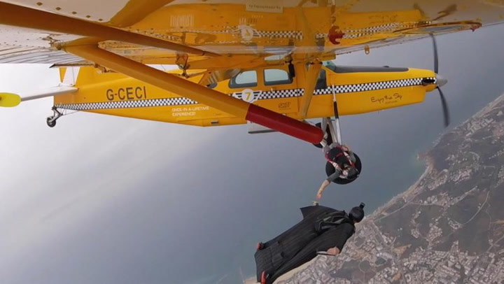 Wingsuit Pilot Passes By A Plane And Hands Off A Banana To One Of The People On Board