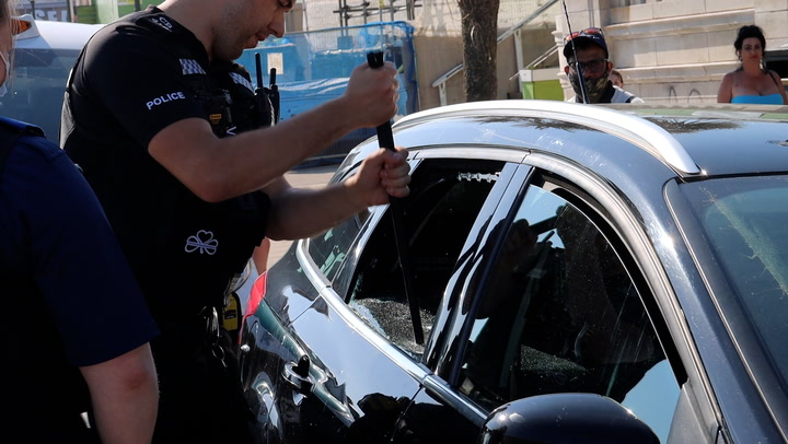 Police smash car window to rescue dogs trapped in 24C heat