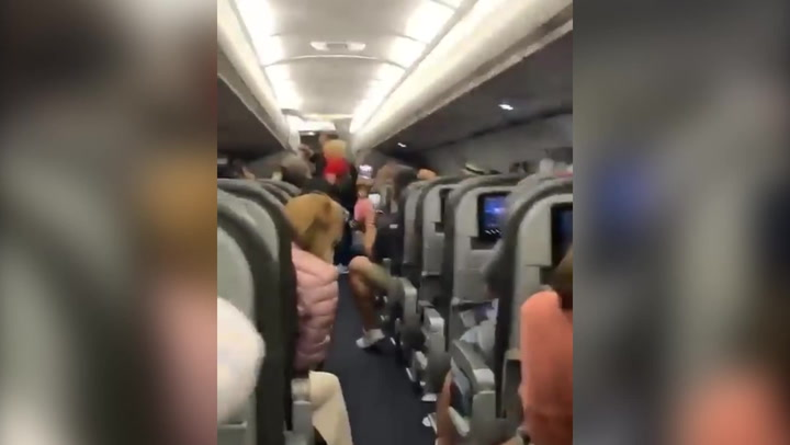 Passengers sing as people who refused to wear face masks are thrown off flight