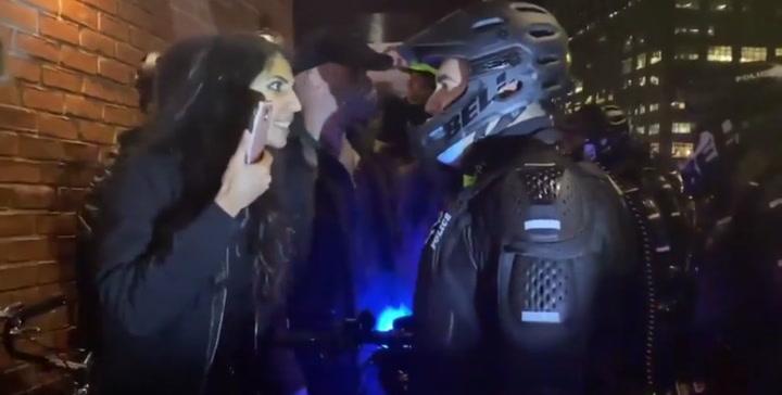 Una chica escupe a un policía antidisturbios en los altercados de Nueva York