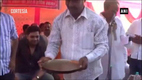Un hombre bebe el agua con la que lava los pies a un diputado de India