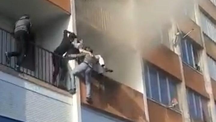 Un grupo de jóvenes trepa por un edificio y salva de las llamas a un anciano desorientado