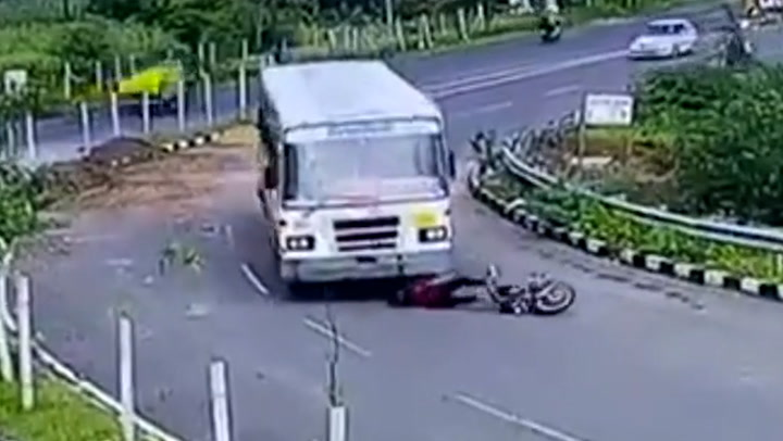 Moment biker has lucky escape after falling under wheels of bus