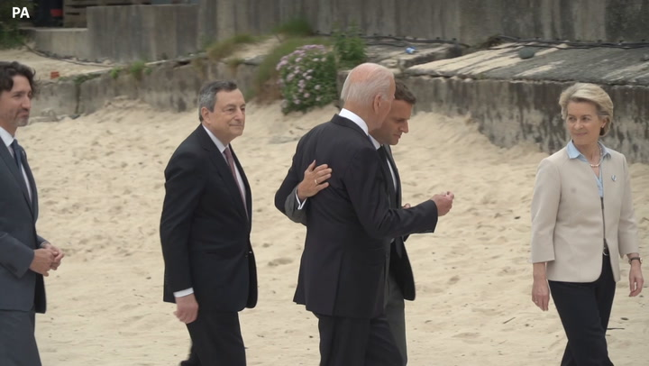 Emmanuel Macron throws his arm around Joe Biden