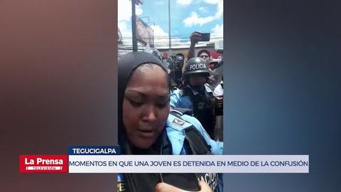 Momentos en que una joven es detenida en medio de la confusión