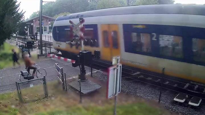 Speeding train narrowly avoids hitting woman running across tracks