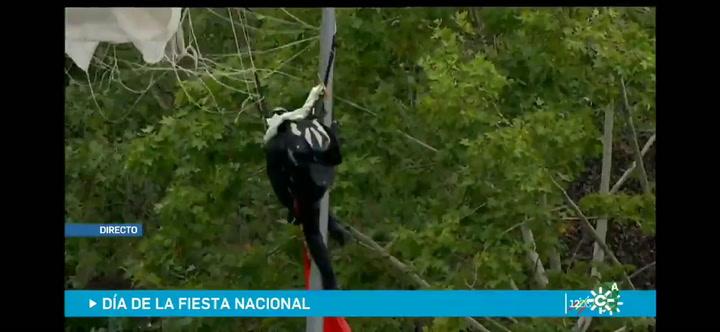 Un paracaidista se queda colgado de una farola en el desfile del Día de la Hispanidad