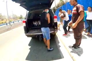 Michaell Chirinos y su agente Paulo Hernández entregan ayuda a personas necesitadas