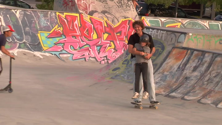 Adorable moment skateboarder averts potential wipeout by scooping up little boy