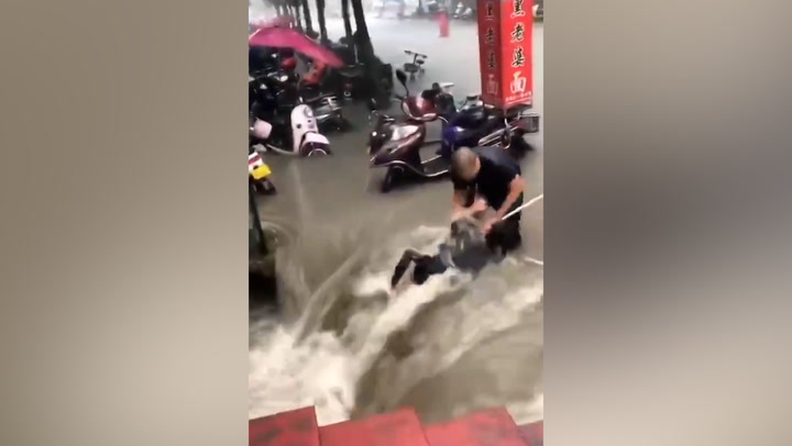 Woman pulled out of raging China flood by rope in dramatic rescue