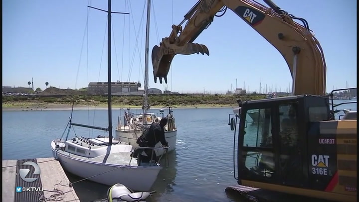 This video of a backhoe smashing up boats in the Oakland Estuary is wild