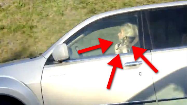 Hun krøller håret bak rattet på motorveien