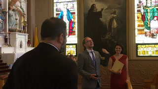 Borek Lizec, Consul General of the Czech Republic in Chicago, gestures as he visits with Czech-Americans at St. John Nepomucene Catholic Church, Pisek, ND Wednesday. Lizec and his wife, Katerina Lizcova Kulhankova, right, stopped in Pisek to meet members of the community and to view Alphonse Mucha's famous painting of Saints Cyril and Methodius. Fr. Jason Lefor of St. John Nepomucene is at left. Click to view full photo. Eric Hylden / Forum News Service