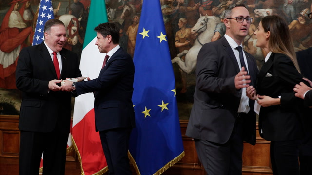 Woman gives Pompeo cheese during photo op with Italian PM