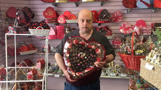Amy Bjorg, general manager at Widman's, holds a 5-pound box of chocolates, the largest box they sell for Valentine's Day. Photo by Eric Hylden/Grand Forks Herald
