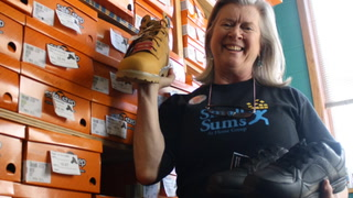 Small Sums Executive Director Terre Thomas holds work shoes Nov. 9, 2017, that are available to homeless clients starting new jobs. The organization's University Avenue office houses dozens of pairs of work shoes and pants. Michael Brun / RiverTown Multimedia
