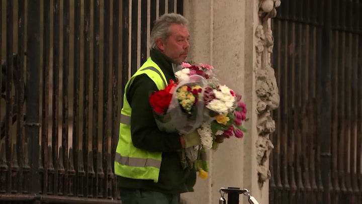 Workers remove flowers from outside Buckingham Palace