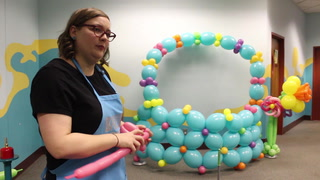 Balloon artist Laural Schultze puts the finishing touches on a large Easter basket made out of balloons that was used at the Lake Superior Zoo as a setting for family photos. Bob King / rking@duluthnews.com