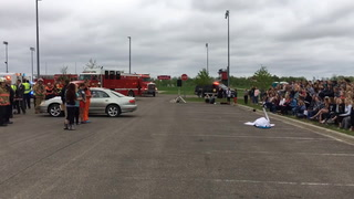 Reggie Habberstad, who works for North Ambulance, gives his daughter, Alexis Habberstad, who was part of the high school's annual mock car crash, a tight hug, as he talks to the crowd of teenagers about what it's like to be a paramedic at the scene of a car crash. (Celeste Edenloff | Echo Press)