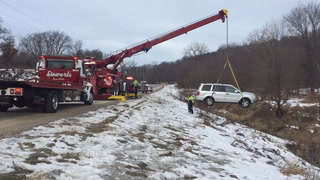 Siewert's Garage uses a rotator to lift a Honda Pilot out of the Hay Creek ditch and onto a flatbed truck along Pioneer Road Friday, Feb. 10, 2017. (photo by Tim Alms)