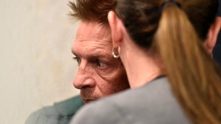 Adam Purinton, 51, is shown in closed circuit TV in court from the Johnson County detention center as Purinton heads towards a room with his public defender, Michelle R. Durrett, left, during his initial court appearance in Olathe, Kan., Feb. 27, 2017. Jill Toyoshiba / The Kansas City Star / Pool