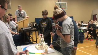 Bryce Sward (left), Kali Scoeck (center) and Brooke Flynn (right), eighth-grade students from Osakis, focus on positioning their prototype so it can grasp and move a wooden block. (Beth Leipholtz / Echo Press)