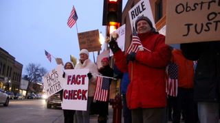 About 50 protesters — comprising residents of communities including Hudson, River Falls and Stillwater — waved signs, flags and rang bells from the sidewalk Nov. 8 in opposition to the latest White House shake-up. Mike Longaecker / RiverTown Multimedia