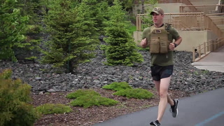 Duluth resident Travis Birr runs on the Lakewalk Tuesday, June 13,  wearing body armor. He'll wear the armor while running Grandma's marathon for Operation: 23 to Zero, which raises awareness about suicide among veterans. (Steve Kuchera / Forum News Service)