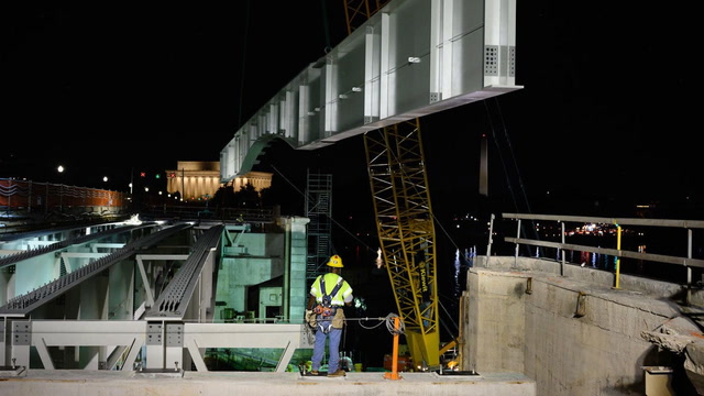 See an iron worker guide an 86-ton monster into place on Memorial Bridge
